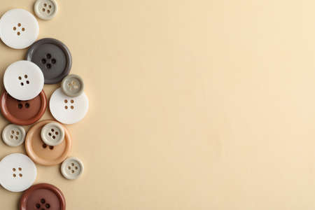 Many colorful sewing buttons on beige background, flat lay. Space for text