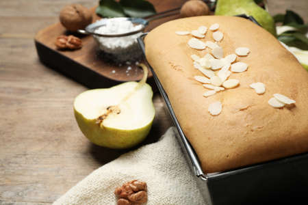 Tasty bread with almond flakes and pear on wooden table, closeup. Homemade cake