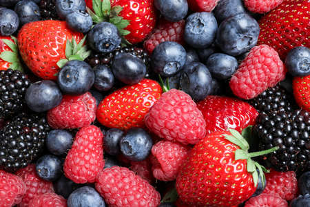 Mix of different ripe tasty berries as background, top view