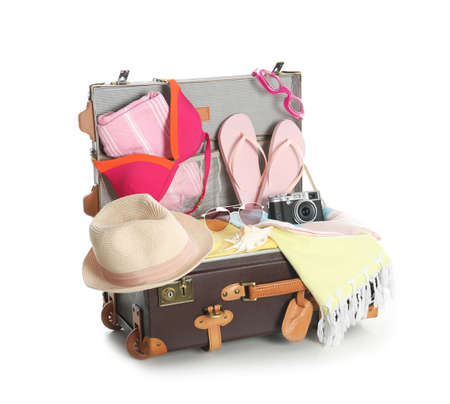 Open vintage suitcase with different beach objects packed for summer vacation isolated on white