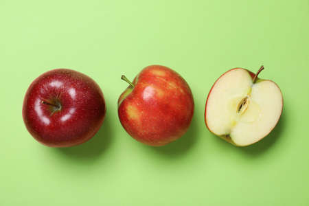 Tasty red apples on green background, flat lay Standard-Bild