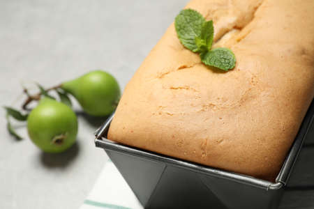 Tasty bread with mint and pears on light gray table, closeup. Homemade cake