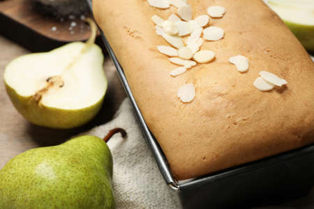 Tasty bread with almond flakes and pears on table, closeup. Homemade cake