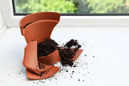 Broken terracotta flower pot with soil on white windowsill indoors
