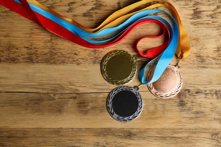 Gold, silver and bronze medals on wooden background, flat lay. Space for design 版權商用圖片