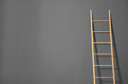 Modern wooden ladder on gray background. Space for text