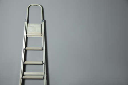Metal stepladder on gray background. Space for text