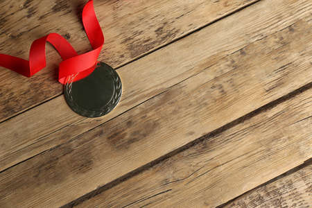 Medal with red ribbon on wooden background, top view. Space for design