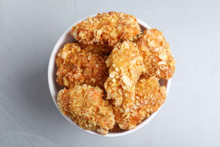 Bucket with yummy nuggets on light background, top view