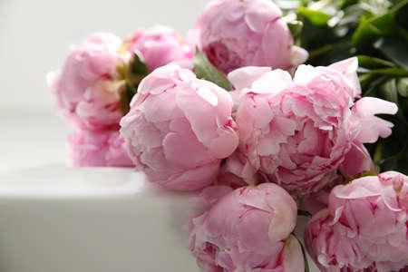 Bouquet of beautiful pink peonies on counter in kitchen, closeup Foto de archivo