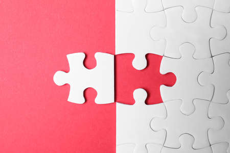 Blank white puzzle with separated piece on red background, flat lay