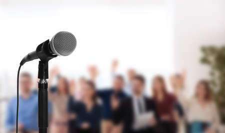 Modern microphone and people at business training indoors, closeup