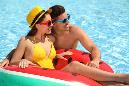 Happy couple with inflatable ring in swimming pool. Summer vacation