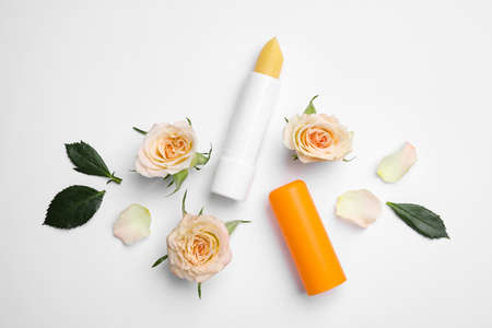 Hygienic lipstick and rose flowers on white background, top view