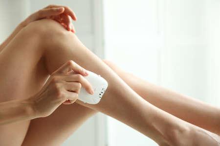 Woman doing leg epilation procedure on light background, closeup Archivio Fotografico