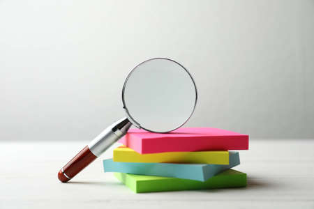 Magnifier glass and stack of colorful memory stickers on white wooden table, closeup. Find keywords concept