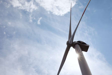 Modern wind turbine against cloudy sky, low angle view. Alternative energy source