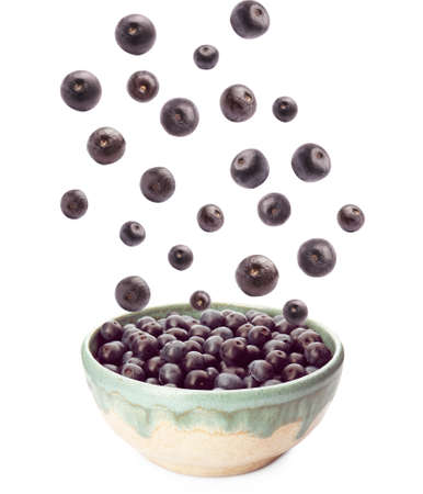 Fresh acai berries falling into bowl on white background