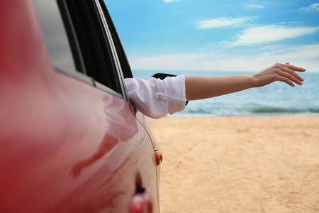 Woman waving from car on beach, closeup. Summer vacation trip