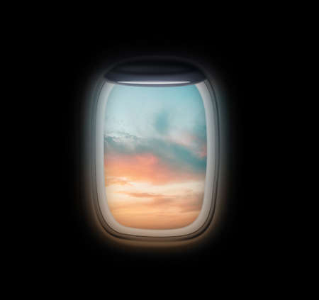 View on beautiful sky through open airplane porthole at sunset