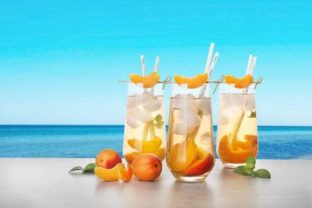 Tasty refreshing drink on table against sea