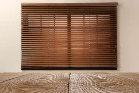 Wooden table and window with blinds on background Stockfoto