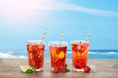 Tasty refreshing drink on wooden table against sea Фото со стока