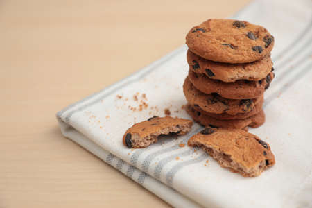 Tasty homemade cookies with chocolate chips on wooden table