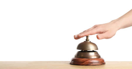 Woman ringing hotel service bell at wooden table