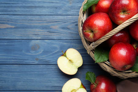 Juicy red apples in wicker basket on blue wooden table, flat lay. Space for text Standard-Bild