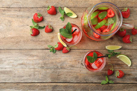 Refreshing drink with strawberry and lime on wooden table, flat lay. Space for text