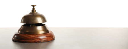 Hotel service bell on gray stone table against white background Stock fotó