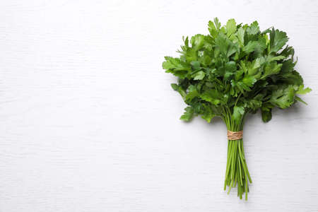 Bunch of fresh green parsley on white wooden table, top view. Space for text