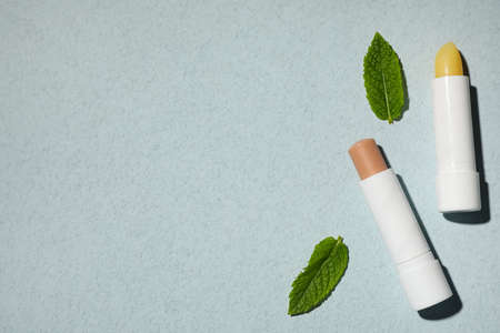 Hygienic lipsticks and mint leaves on light green background, flat lay. Space for text Zdjęcie Seryjne