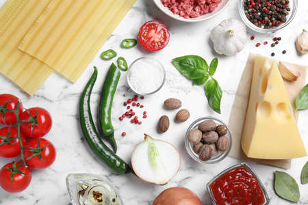 Fresh ingredients for lasagna on white marble table, flat lay