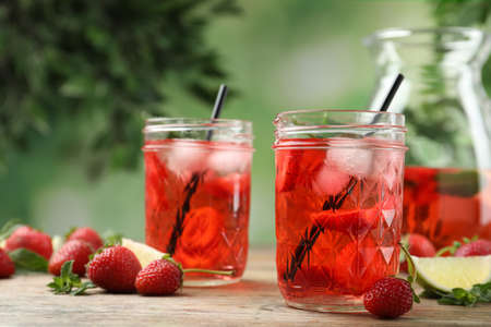 Refreshing drink with strawberry and lime on wooden table