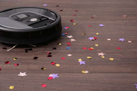 Modern robotic vacuum cleaner removing confetti from wooden floor. Space for text
