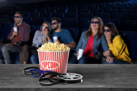Popcorn, 3D glasses, movie reel on table and young people in cinema hall