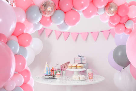 Baby shower party for girl. Tasty treats on table in room decorated with balloons