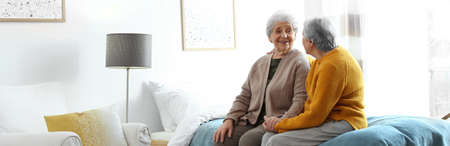 Elderly women spending time together in bedroom, banner design. Senior people care