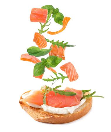 Tasty bruschetta with flying ingredients on white background