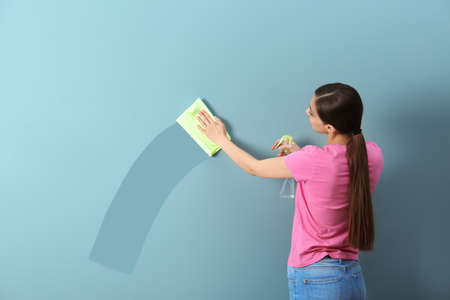 Young woman wiping color wall with rag. Cleaning service Foto de archivo