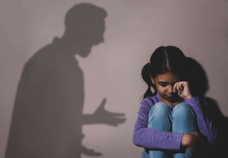 Child abuse. Father yelling at his daughter. Shadow of man on wall