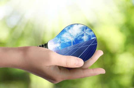 Alternative energy source. Woman holding light bulb with solar panels and wind turbines, closeup Stock fotó