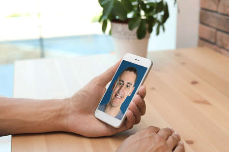 Man using smartphone with facial recognition system at table indoors, closeup. Biometric verification