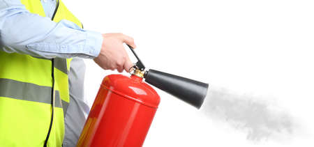 Worker using fire extinguisher on white background, closeup