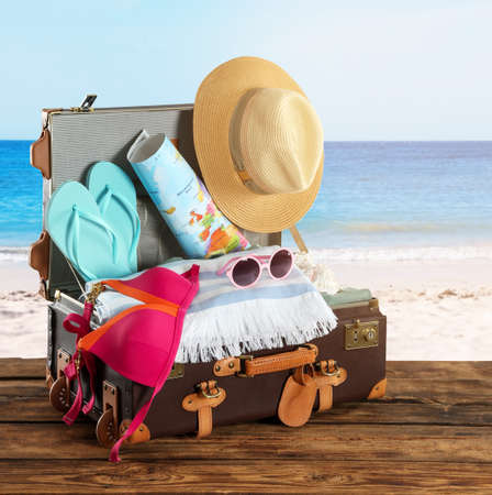 Open vintage suitcase packed for summer vacation on wooden surface against sandy beach