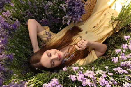 Young woman lying in lavender field on summer day, top view