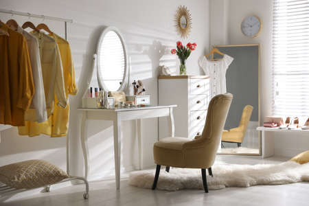 Stylish room interior with elegant dressing table, mirror and comfortable chair Stock fotó