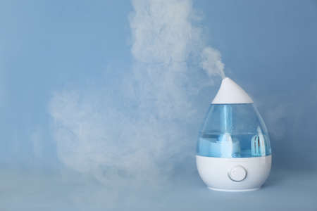 Modern air humidifier on light blue background. Space for text